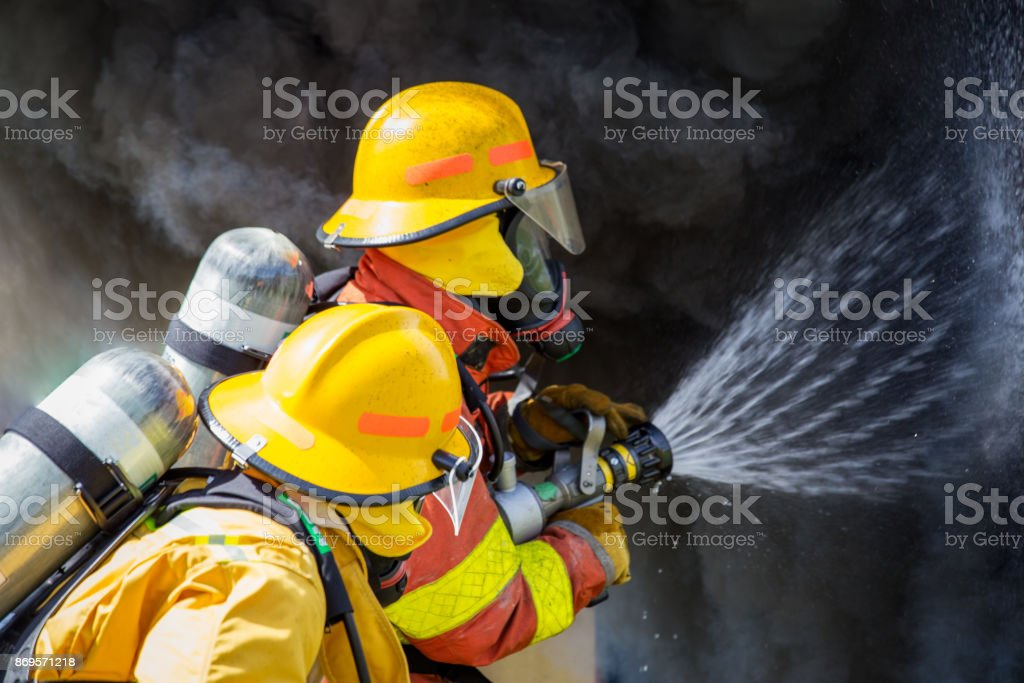 two firefighters water spray by high pressure nozzle to fire surround with smoke and copy space stock photo