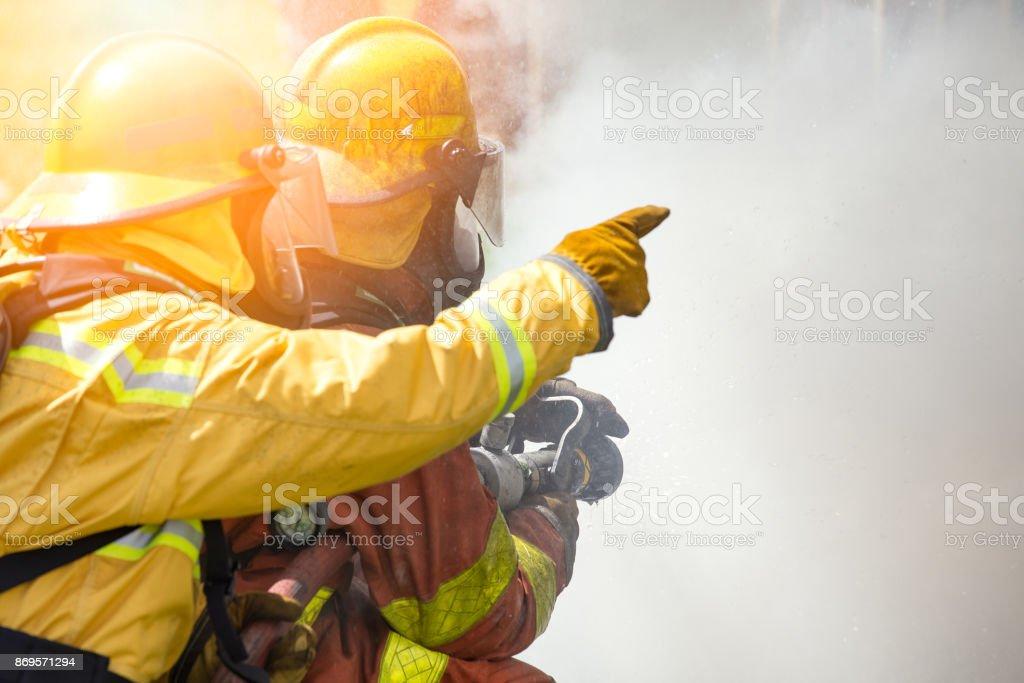 zwei Feuerwehrleute Wasserspray von Hochdruckdüse, umgeben von Rauch mit Fackel und Kopie Raum Feuer – Foto