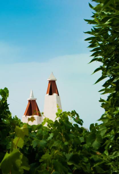 zwei kamine auf den dächern der stadt en porter von der insel menorca - dachschräge einrichten stock-fotos und bilder