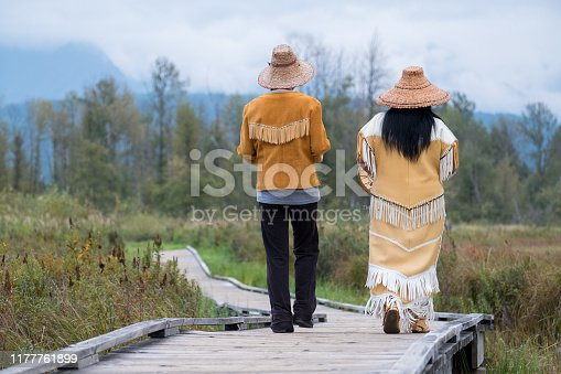 Two Indigenous Canadian woman walk together on the boardwalk by the lake. They are both dressed in traditional clothing. They are both thankful for their heritage