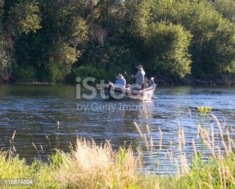 istock Two fishermen and a dog in fishing boat 115874504