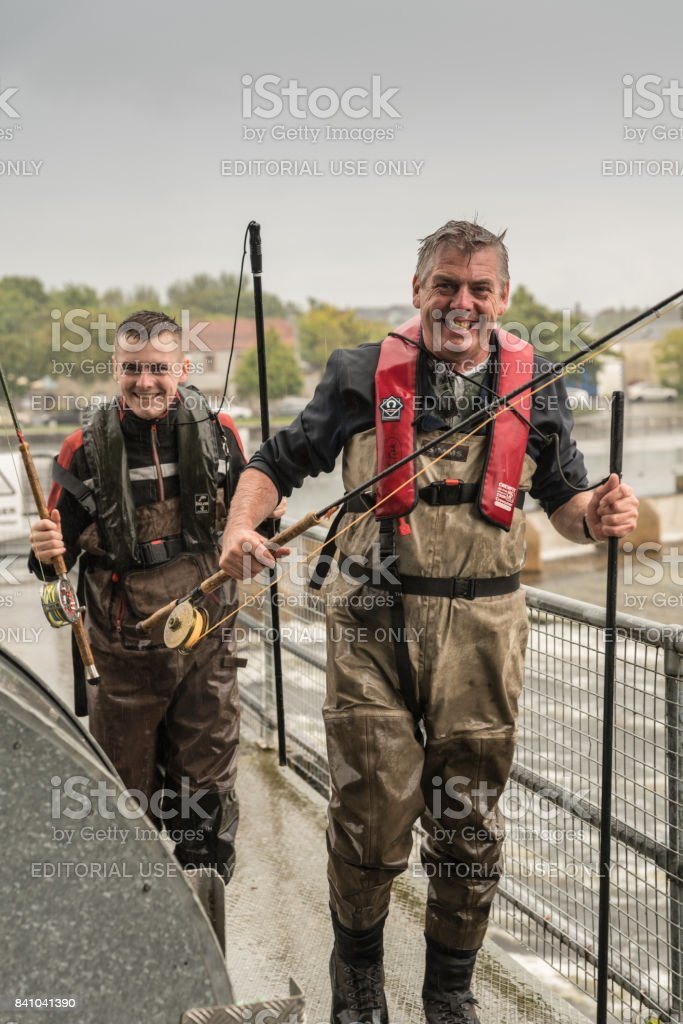Two fishermen flee heavy rain on Corrib River. Galway Ireland. stock photo