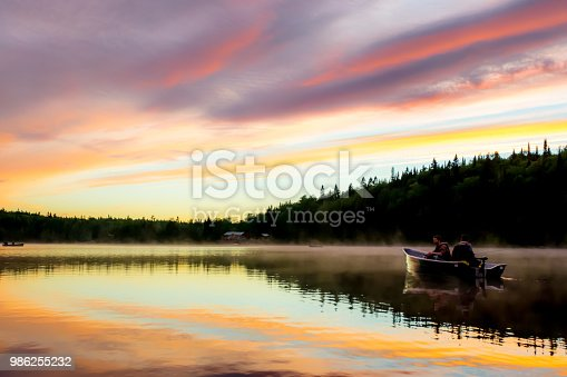 Two fishermen on a peaceful lake with a multicoloured sky sunset and a chalet in background. Quebec, Canada