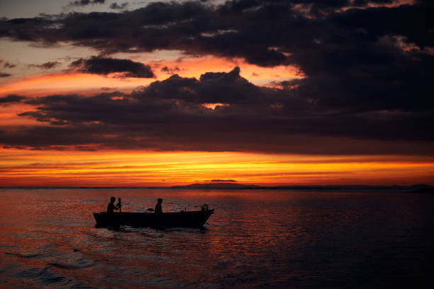 Two fishermen return home at sunset. Art view on tropic nature.Tarcoles river, Costa Rica. stock photo