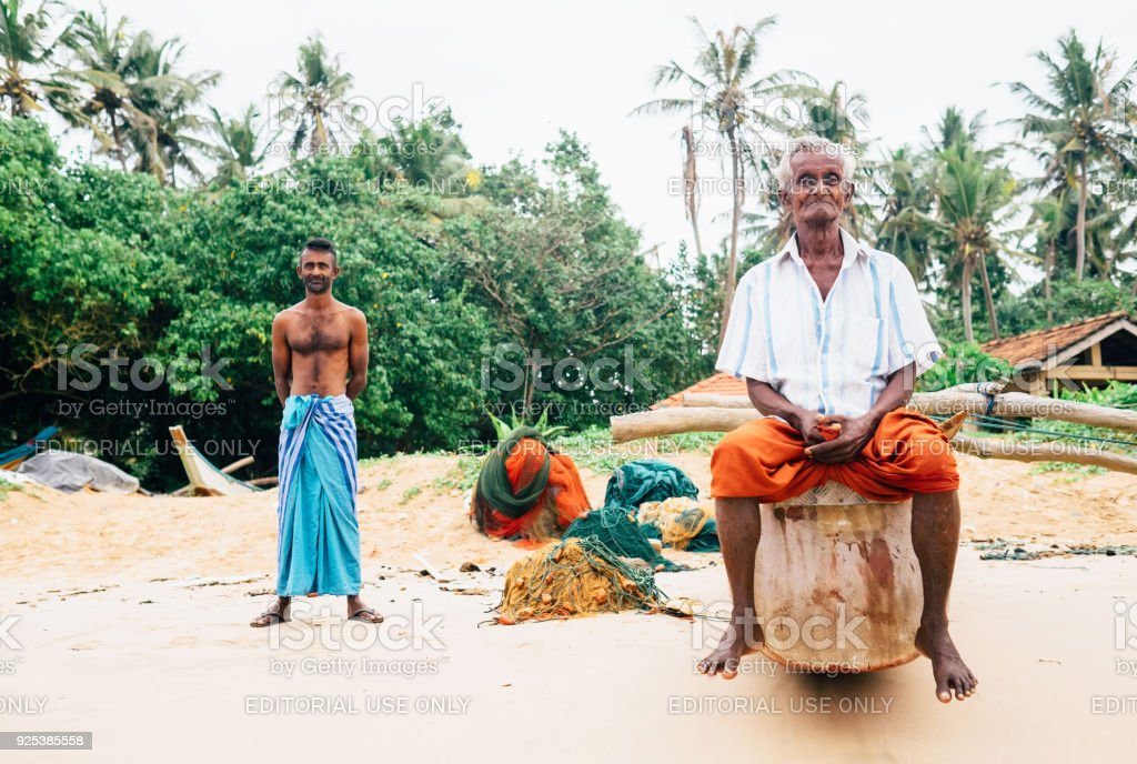 Two Fishermen standing on the beach after the fishing in the morning time in Weligama, Sri Lanka stock photo
