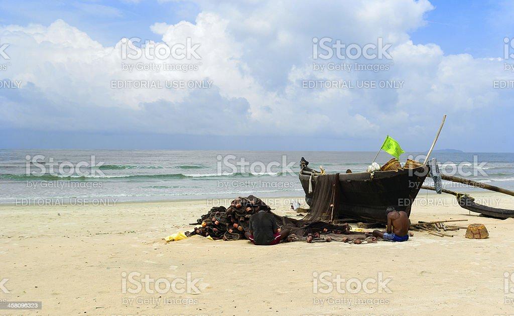 Two fishman near traditional boat.Goa royalty-free stock photo