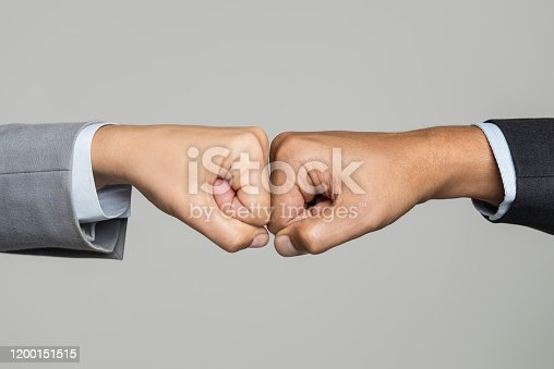 Two unrecognizable caucasian business peoples fits are touching each other in front of white background. One businessperson is wearing gray suit. The other is wearing a black suit.
