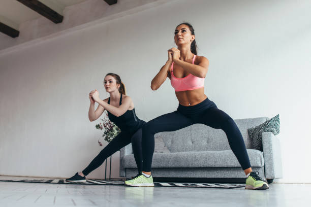 Two fit girls doing home workout performing lateral lunges at home. stock photo