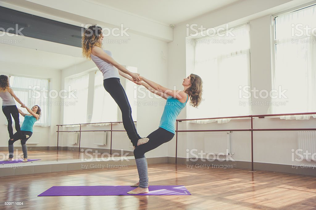 Two fit pretty women are doing balance exercise stock photo