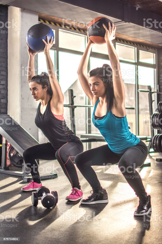 Two fit sporty girls exercising together with pilates balls in the gym. stock photo