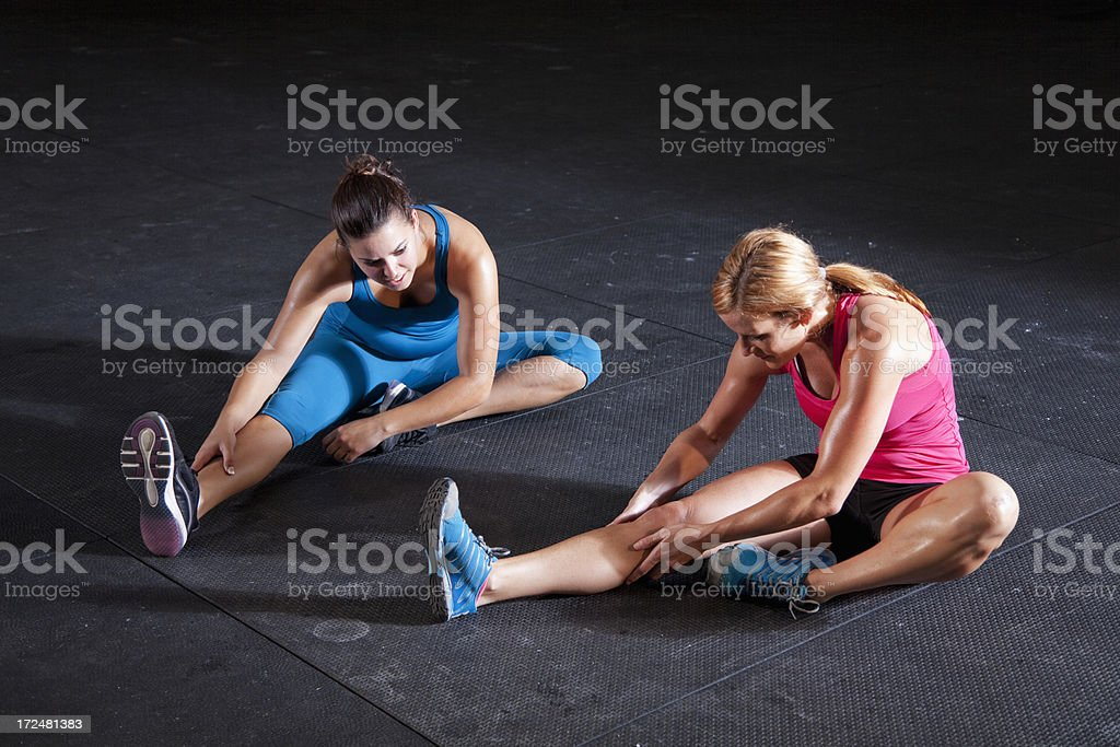 Two fit woman in gym stretching stock photo