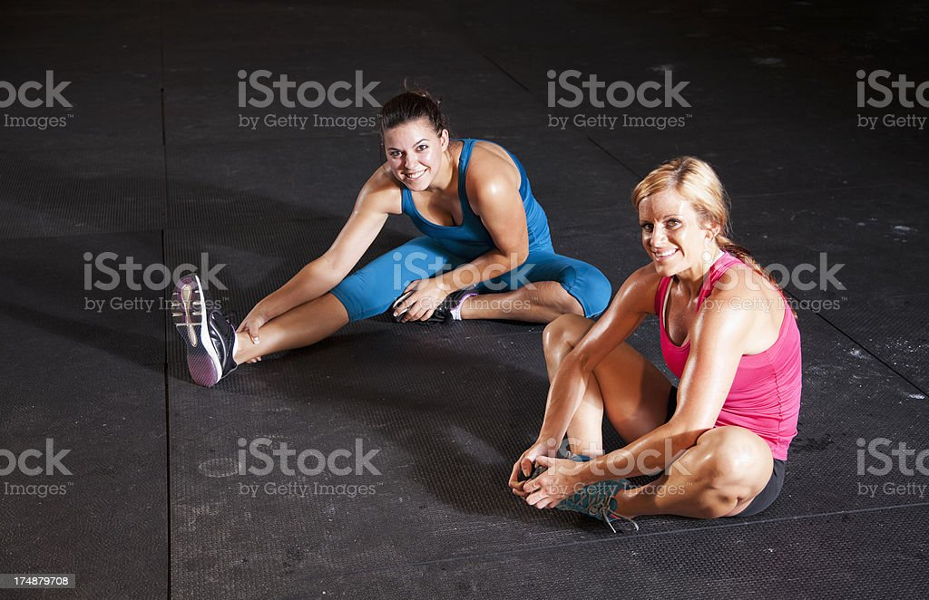 Two fit woman in gym stretching royalty-free stock photo