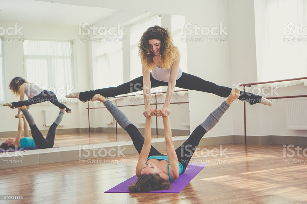 Two fit women are doing balance exercise stock photo