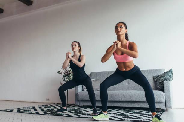 Zwei Fit Frauen zusammen trainieren Kniebeugen zu Hause tun – Foto