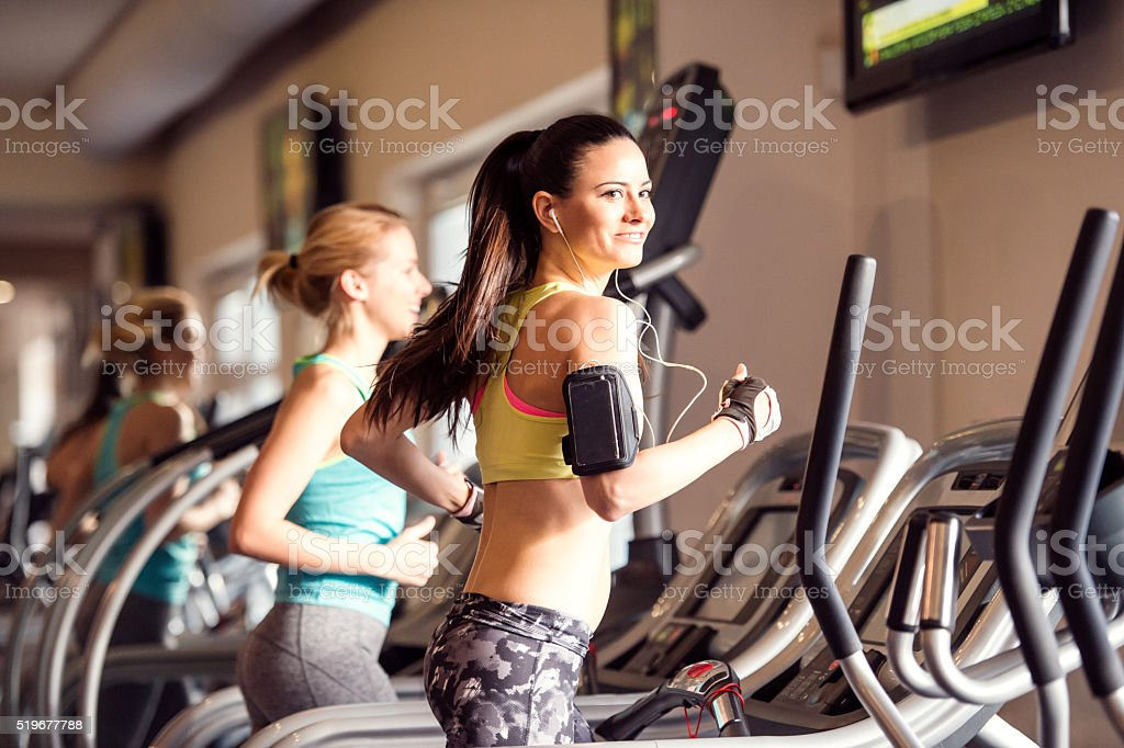 Two fit women running on treadmills in modern gym royalty-free stock photo