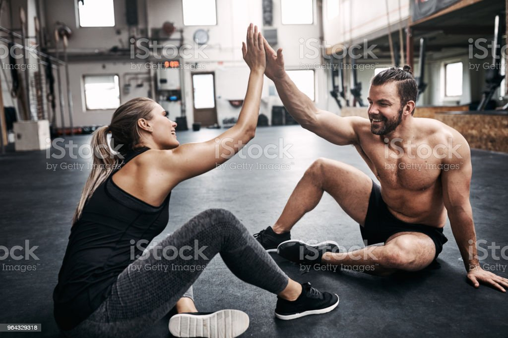 Two fit young people in sportswear smiling and high fiving together...