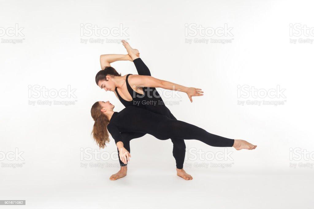 Two flexibility friends dancing, doing performance. Studio shot,...