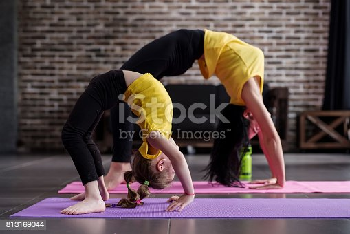 istock Two flexible girls of different age doing upward facing bow yoga pose working out 813169044