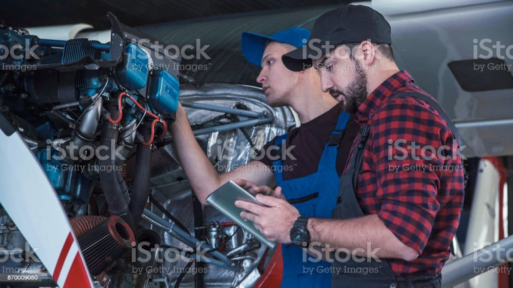 Two flight mechanics doing a pre flight check stock photo
