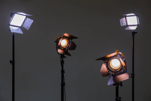 Two floodlights with halogen lamps and Fresnel lens and two led lighting device. Shooting in the interior on a gray background