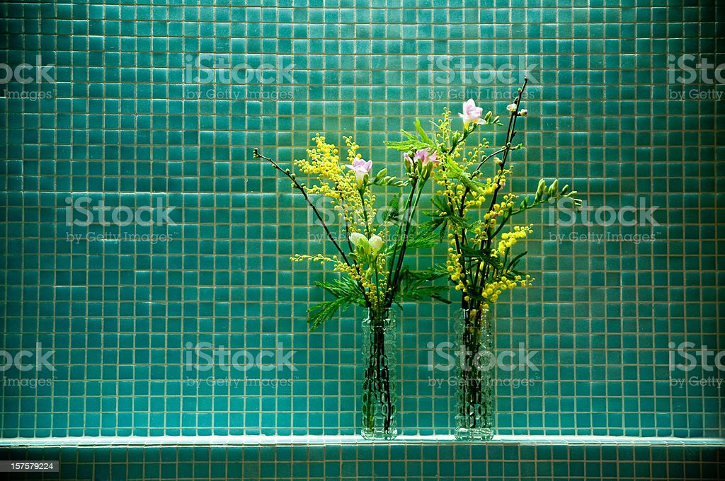 two flower bunches in front of glass tiles royalty-free stock photo
