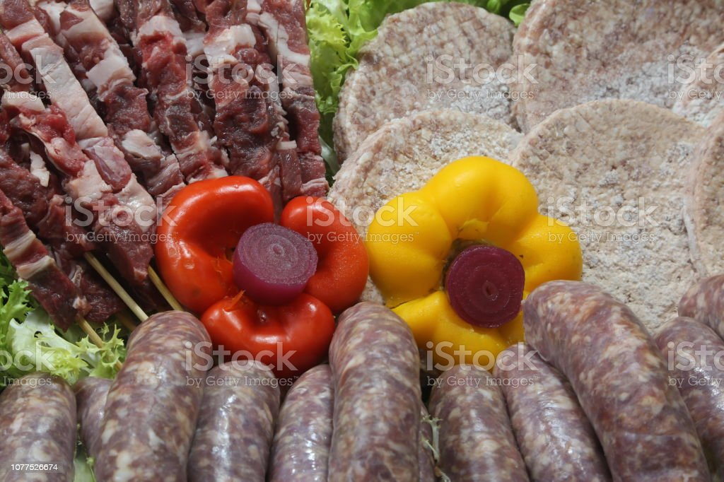 two flower-shaped peppers in the butcher s shop with raw sausage - foto stock