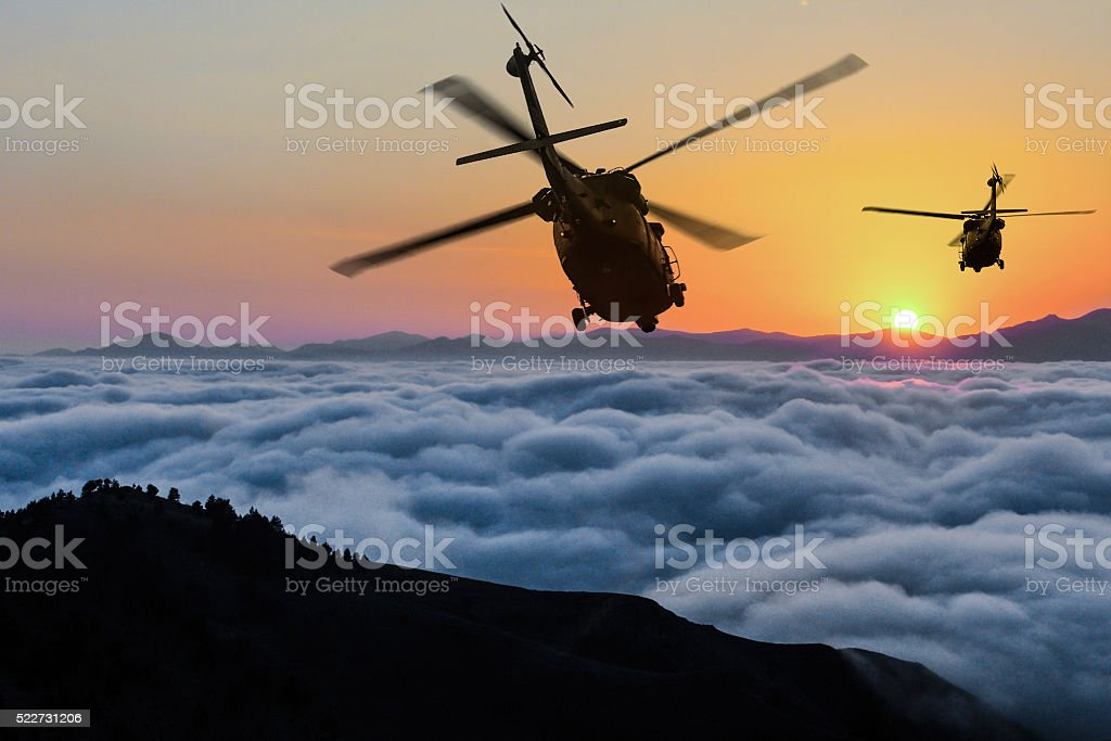 Two flying army helicopters at sunset stock photo