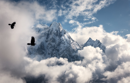 Two flying birds against majestical Manaslu mountain with snowy peak in clouds in sunny bright day in Nepal. Landscape with beautiful high rocks and blue cloudy sky. Nature background. Fairy scene