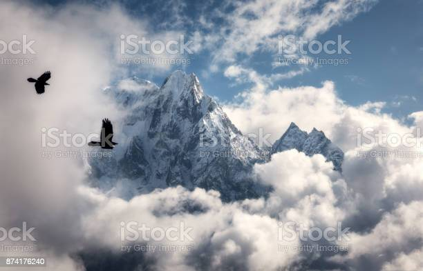 Photo of Two flying birds against majestical Manaslu mountain with snowy peak in clouds in sunny bright day in Nepal. Landscape with beautiful high rocks and blue cloudy sky. Nature background. Fairy scene