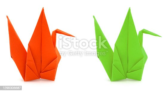 Two folded colorful origami cranes on white