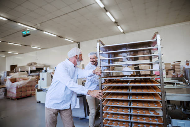 Two food plant employees pushing trays with fresh cookies. Food plant interior. Two food plant employees pushing trays with fresh cookies. Food plant interior. food warehouse stock pictures, royalty-free photos & images