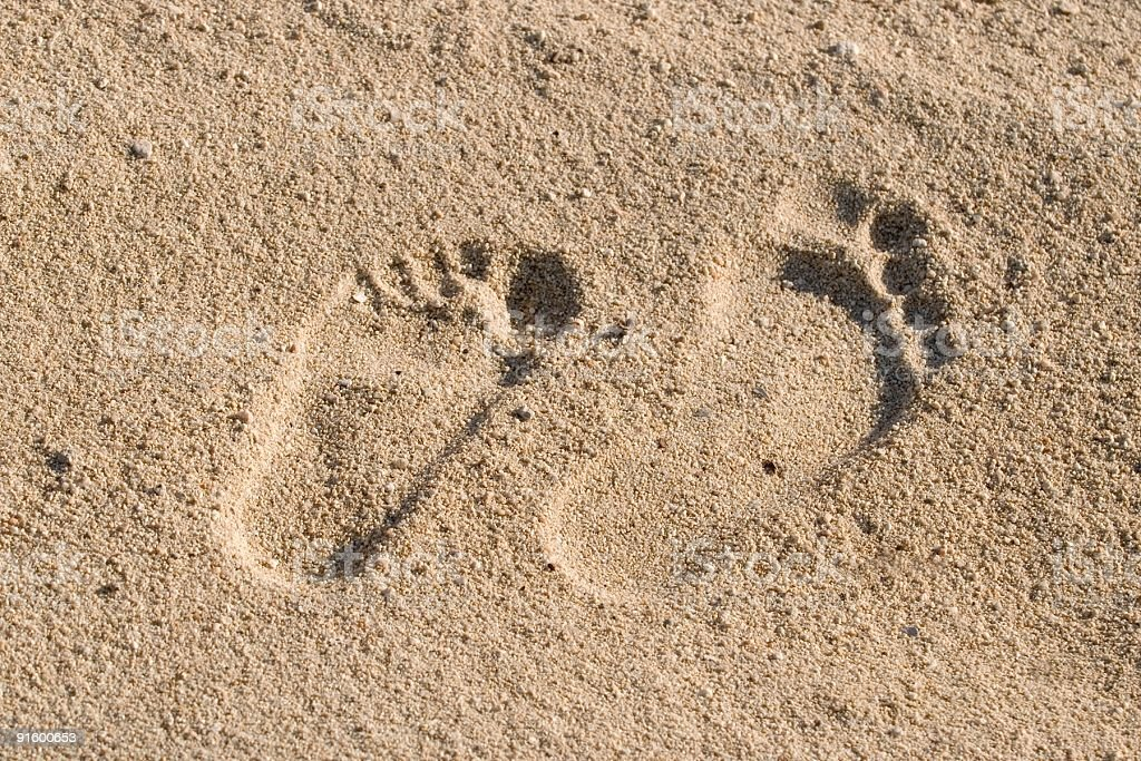 two foot steps in the sand royalty-free stock photo