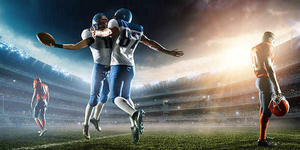 Two Football Players celebrate their victory Two Football Players celebrate their victory. The action takes place on professional stadium. The opposite team players are sad. Players wear unbranded sports uniform. There is artificial light on stadium together with sunlight. quarterback stock pictures, royalty-free photos & images