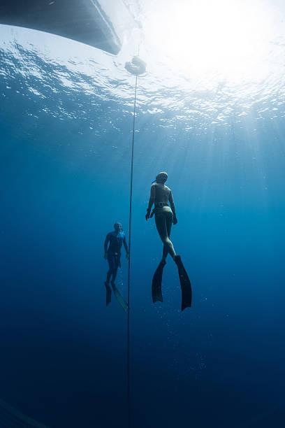 two free divers swim under the water - freitauchen stock-fotos und bilder