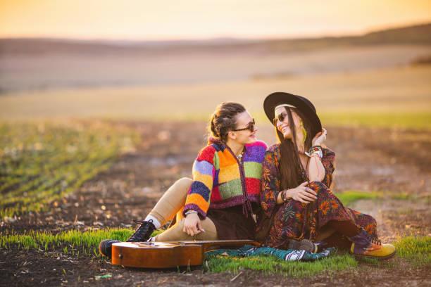 två fria hippie kvinnor relaxin på fältet - happy indie pop bildbanksfoton och bilder