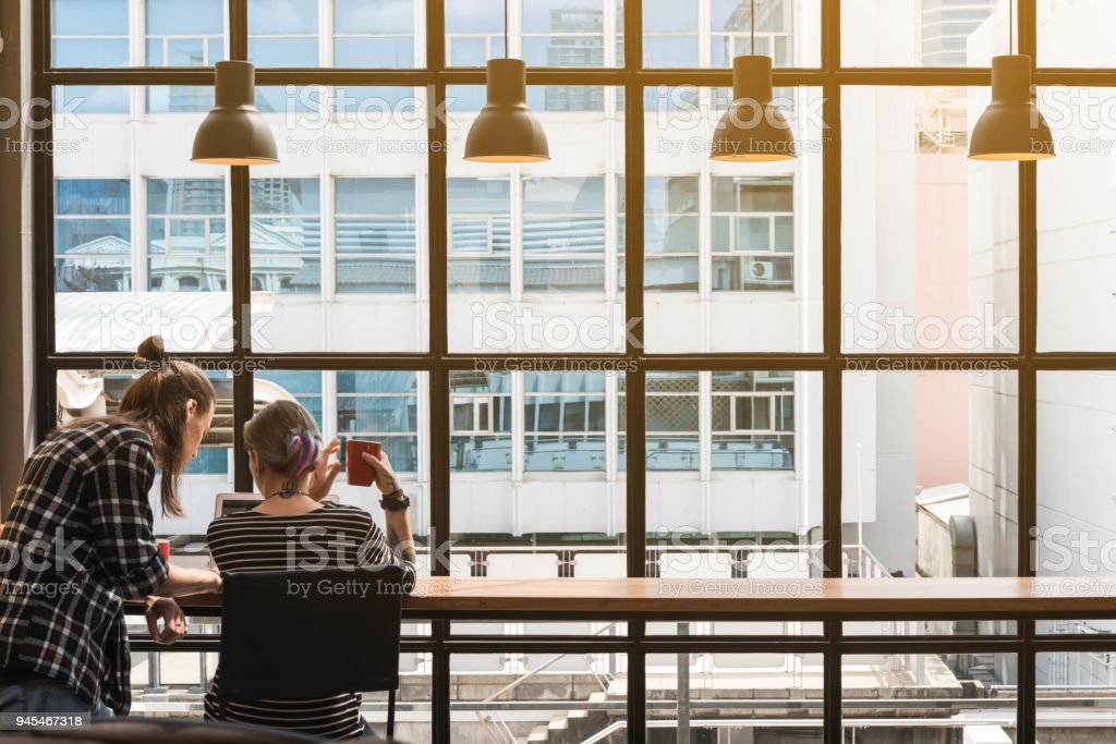Dos freelance trabajando en cafetería, trabajador nómada conceptual, par divertirse trabajar juntos en la cafetería - foto de stock