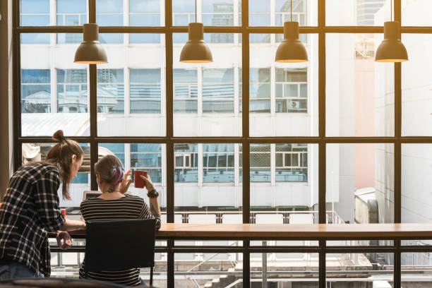 Two freelance working in coffee shop, Nomad worker conceptual, couple having fun work together in cafe stock photo