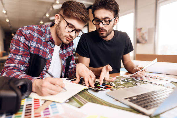 Two freelancer men looking at color swatches at laptop at desk. stock photo