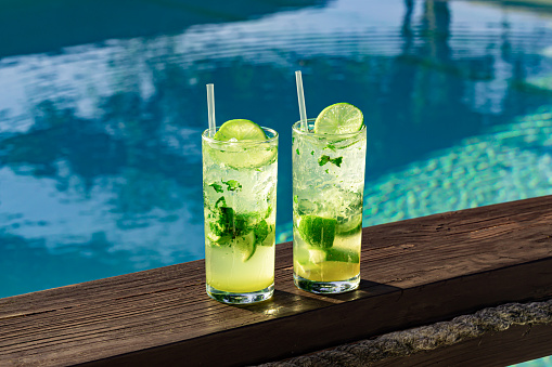 Two fresh and cool mojitos with ice cubes, lime slices and mint leaves on a turquoise pool background