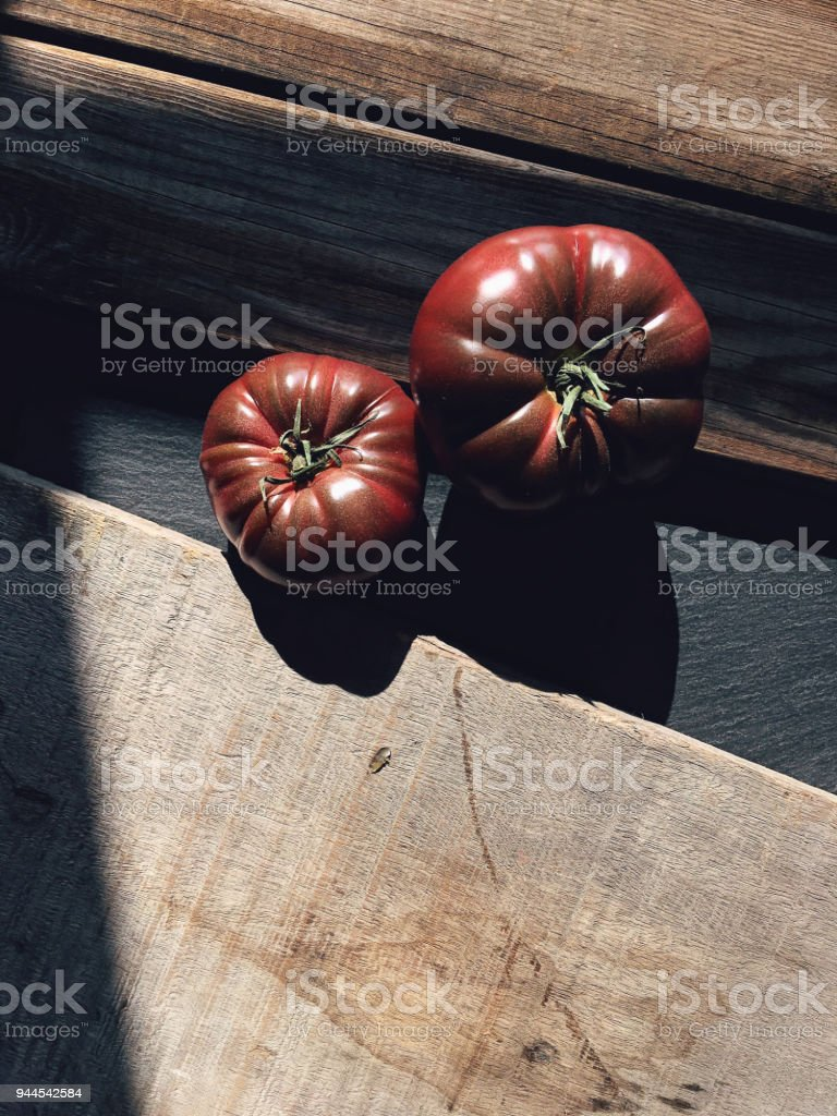 Two fresh dark tomatoes on wooden table stock photo