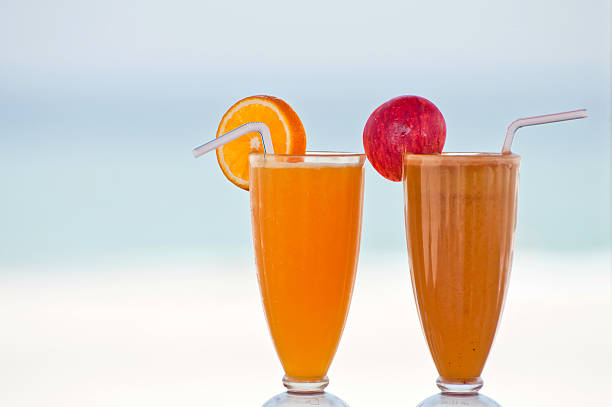 Two fresh fruit juices on a beach