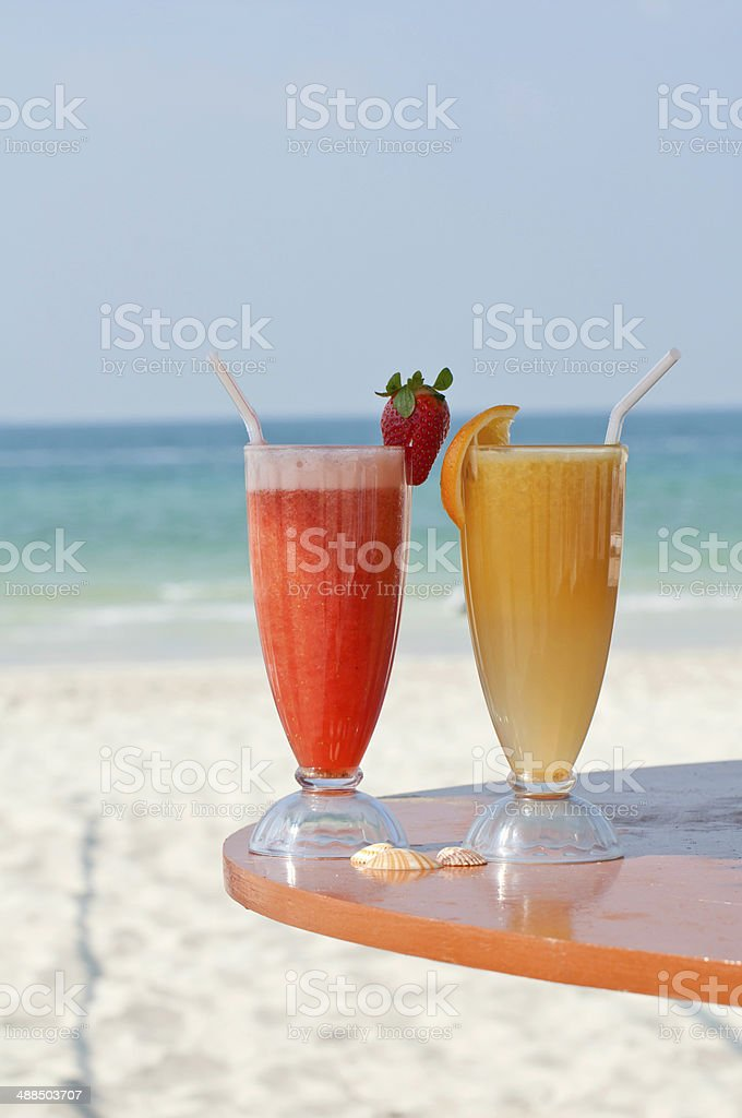 Two fresh fruit juices on a beach stock photo
