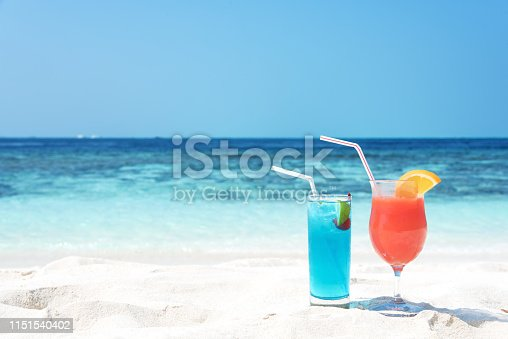 Two fresh fruity cocktails on the tropical sandy beach
