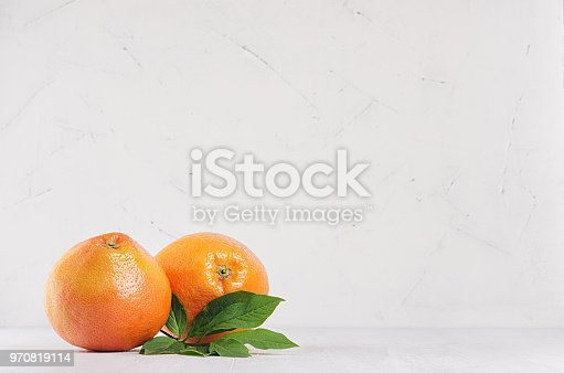 istock Two fresh glossy whole grapefruits on white wooden background with copy space. 970819114