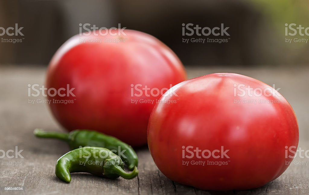 Two fresh home-grown tomatoes and spicy green chili peppers royalty-free stock photo