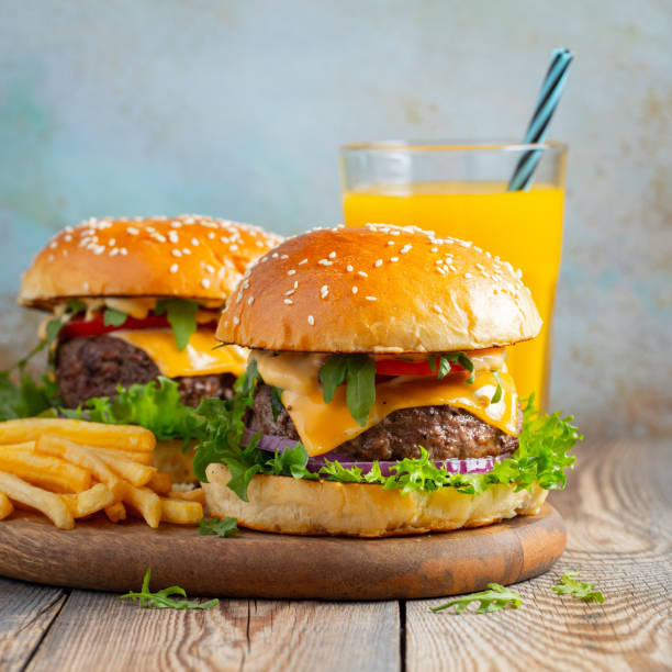 two fresh homemade burgers with fried potatoes and orange juice on a wooden table - onion juice stock photos and pictures