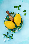 Two fresh lemons in blue plate on turquoise concrete background. Food background. Top view.