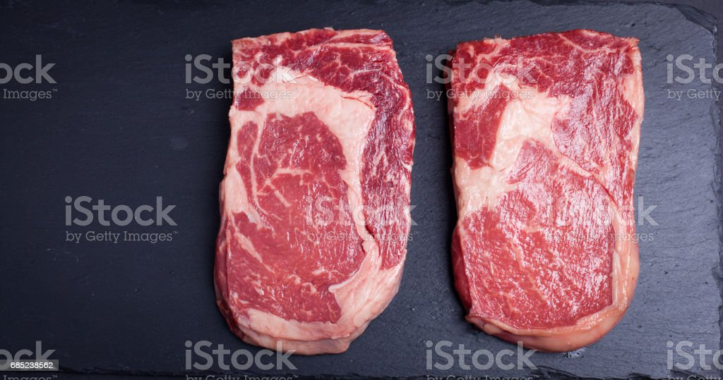 Two fresh raw marble meat, black Angus ribeye steak on a dark stone background. royalty-free stock photo