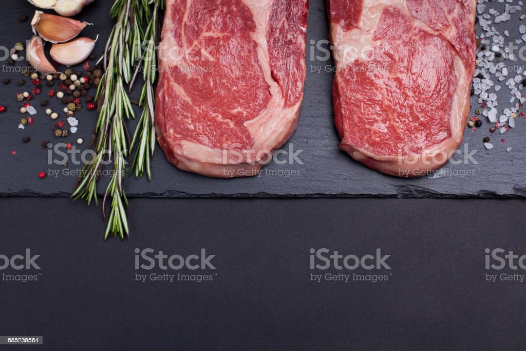 Two fresh raw marble meat, black Angus ribeye steak with spices on a dark stone background. royalty-free stock photo