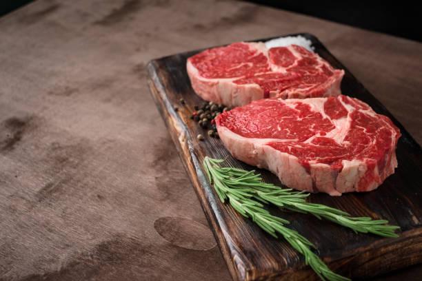twee verse rauwe rib-eye steak op houten bord op houten achtergrond met zout, peper en rosmary in een rustieke stijl - vleesdelen stockfoto's en -beelden
